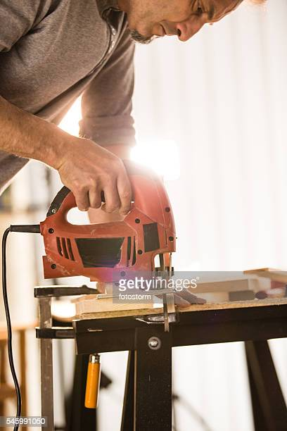 Male woodworker cutting a piece of wood using a jigsaw