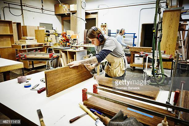 Male woodworker sanding edge of custom shelving