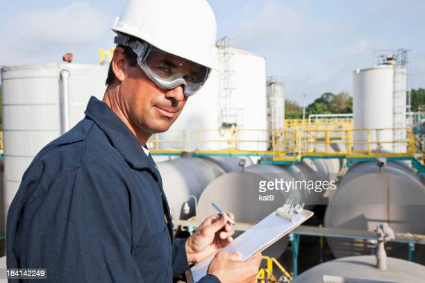 Male worker at industrial plant writing on clipboard