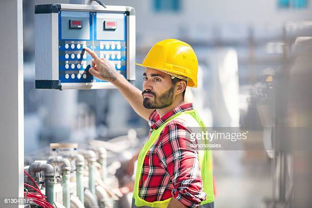 Male worker carefully operating a machine in factory