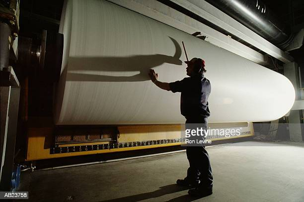 Male worker checking sheets of pulp in paper mill, rear view