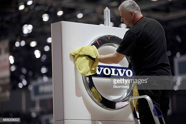 A male worker cleans a Volvo logo as it sits on a sign at the Volvo Cars display stand ahead of the 85th Geneva International Motor Show in Geneva...