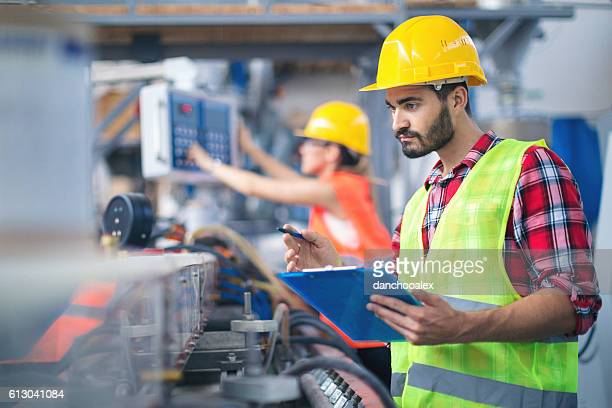 Male worker in factory taking notes