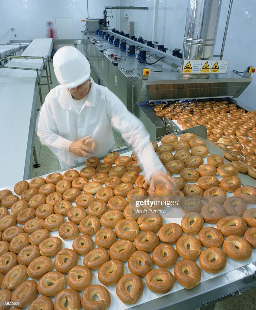 Male worker in protective clothing at bagel factory, elevated view : Stock Photo