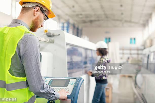 Masculino trabalhador utilizar uma máquina em fábrica