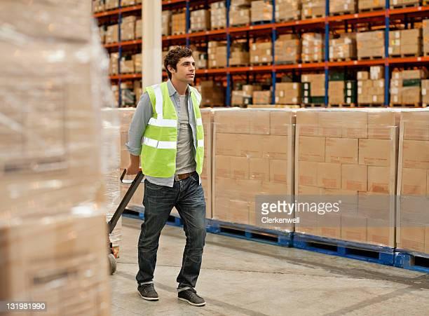 Homme Travailleur tirant Diable au warehouse