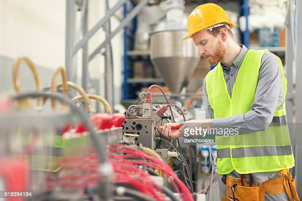 Männliche Arbeiter reparieren eine Maschine in der Fabrik