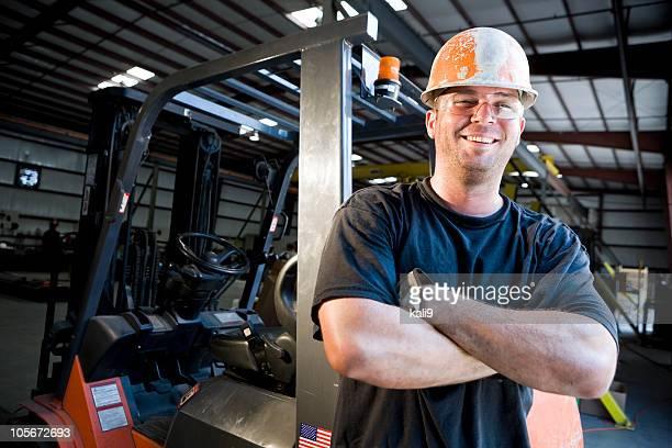 Lavoratore maschio in piedi di carrelli elevatori in magazzino