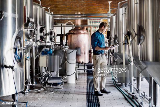 Male worker using digital tablet in brewery