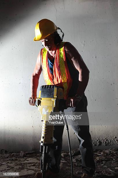 Male worker using jackhammer in tunnel
