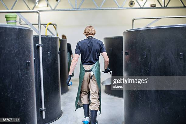 Male worker walking through hatchery tanks in fish farm