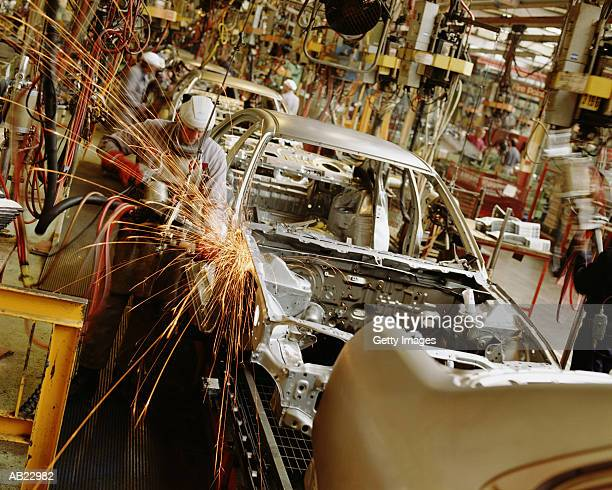 Male workers on car assembly line in manufacturing plant