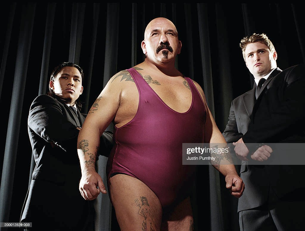 Male wrestler flanked by two bodyguards : Stock Photo