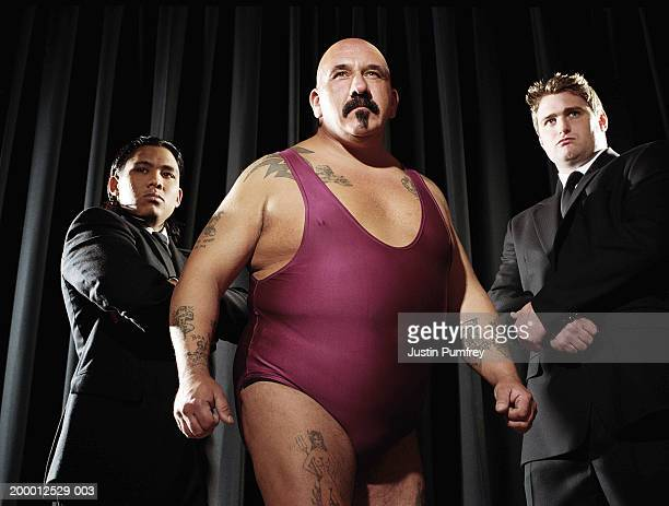 Male wrestler flanked by two bodyguards