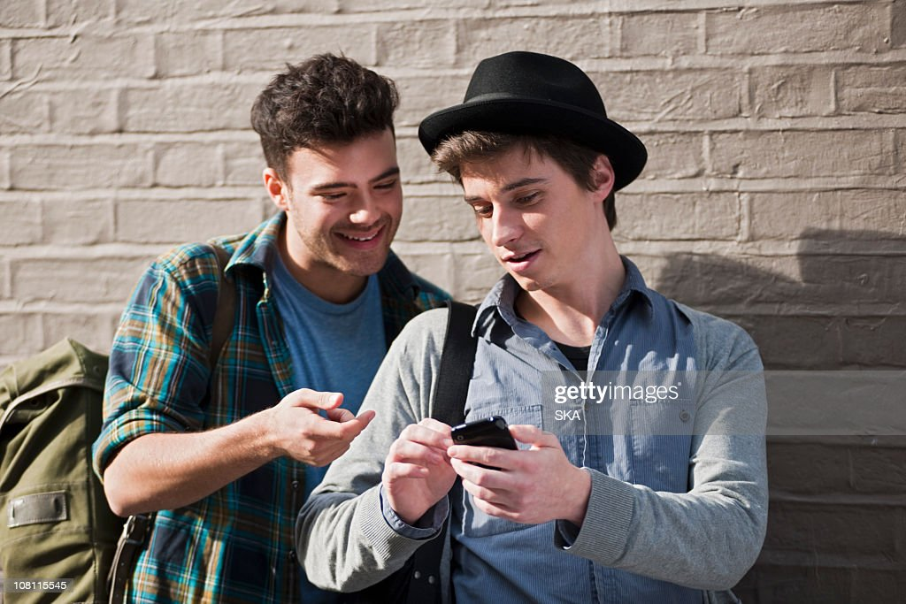 2 males sharing mobile device outside : Stock Photo
