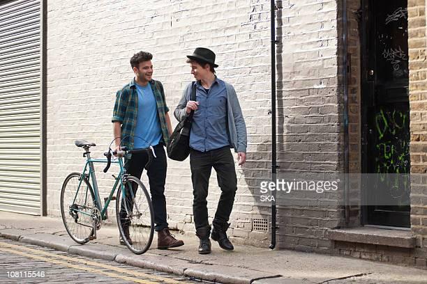 2 males walking in street, talking