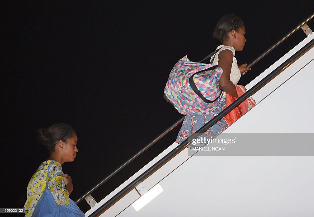 Malia (L) and Sasha (R), the daughters of US President Barack Obama and First Lady Michelle Obama, board Air Force One on January 5, 2013 upon departure from Hickam Air Force Base in Honolulu, Hawaii. There Obamas were to return to Washington, DC after vacationing in Hawaii. AFP PHOTO / Mandel NGAN