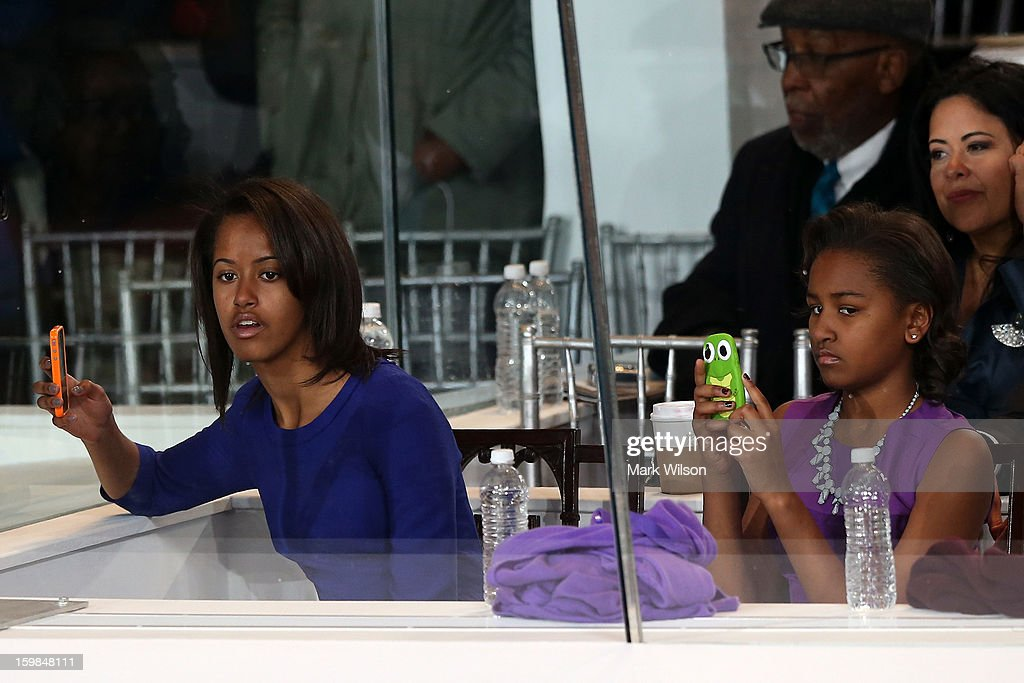 Malia Obama (L) and Sasha Obama watch the presidential inaugural parade from a reviewing standl January 21, 2013 in Washington, DC. Barack Obama was re-elected for a second term as President of the United States.