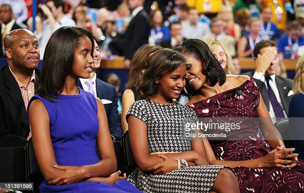 Malia Obama Sasha Obama and First lady Michelle Obama listen as Democratic presidential candidate US President Barack Obama speaks on stage during...