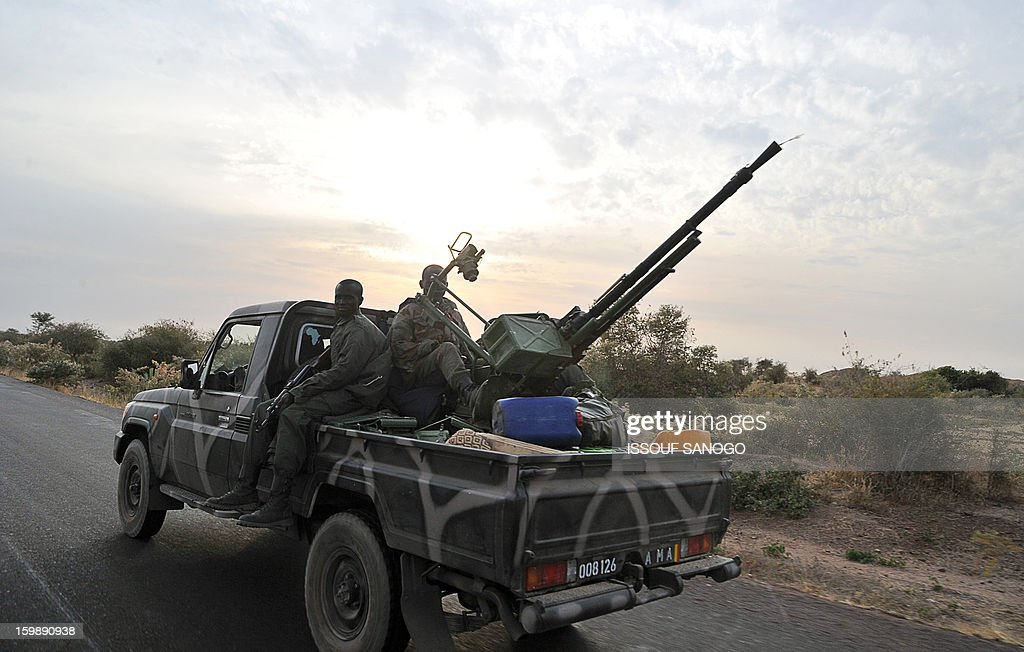 A Malian army armed pickup truck drives near Markalaon on January 22, 2013. Italy said Tuesday it will send three planes to Mali to help support French and Malian troops battling Islamist rebels after parliament gave the green light for a two- to three-month logistical mission. AFP PHOTO / ISSOUF SANOGO