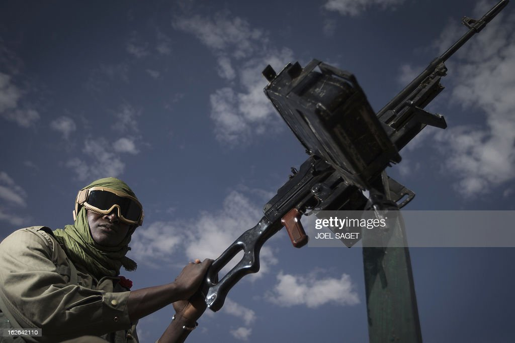 Malian army gunner Modibo Tangara, aged 22, stands beside a gun machine on February 25, 2013 in Gao, some 1,200 kilometres (745 miles) north of Bamako. After recapturing the north's cities from the Al Qaeda groups that had controlled them since April 2012, the six-week-long French-led offensive took the fight to the retreating Islamist insurgents' toughest desert bastions. AFP PHOTO / JOEL SAGET