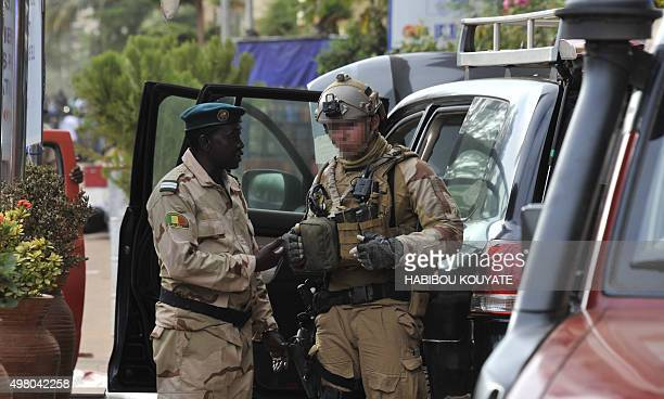 A Malian army officer speaks to a member of French special forces at the entrance the Radisson Blu hotel in Bamako on November 20 after the assault...