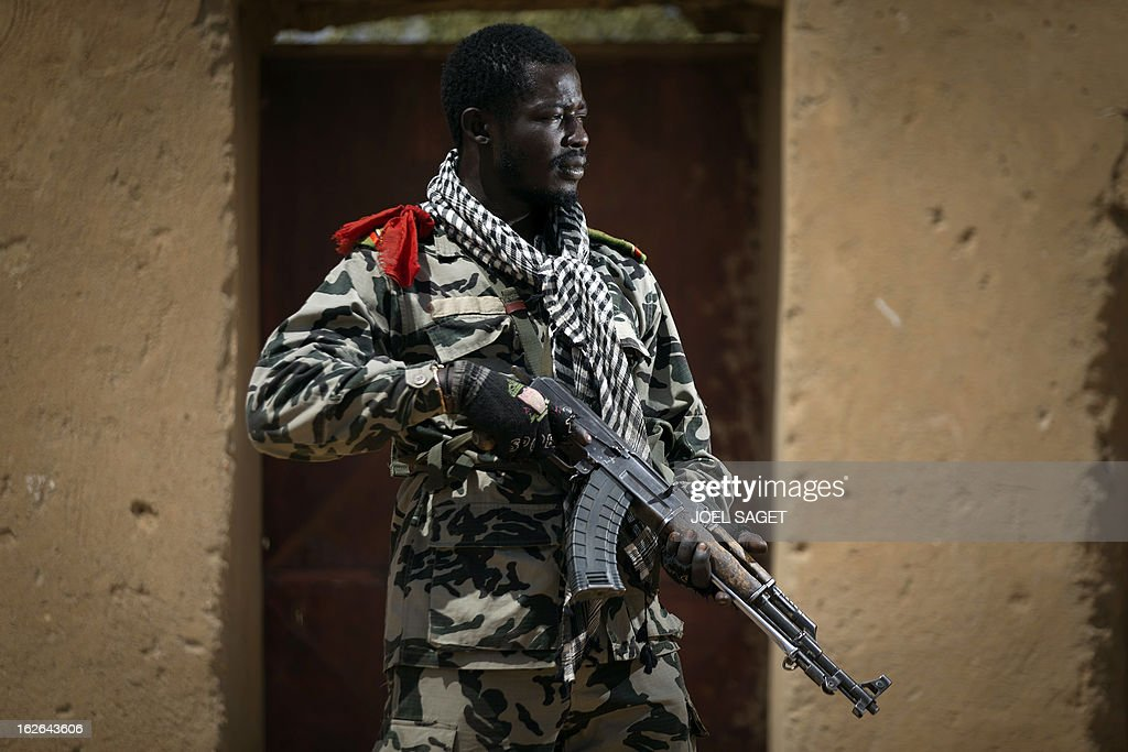Malian army paratrooper Ousmane Sangare, aged 26, holds an AK-47 assault rifle on February 25, 2013 in Gao, some 1,200 kilometres (745 miles) north of Bamako. After recapturing the north's cities from the Al Qaeda groups that had controlled them since April 2012, the six-week-long French-led offensive took the fight to the retreating Islamist insurgents' toughest desert bastions.