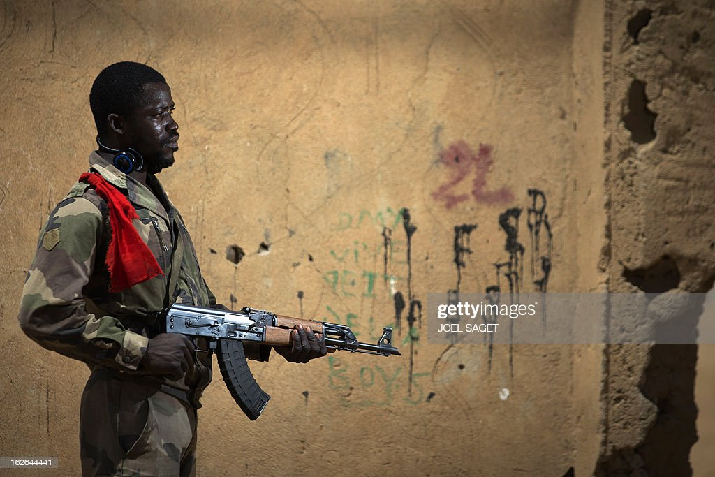 Malian army paratrooper Soumaila Coulibaly, aged 26, poses with an AK-47 assault rifle on February 25, 2013 in Gao, some 1,200 kilometres (745 miles) north of Bamako. After recapturing the north's cities from the Al Qaeda groups that had controlled them since April 2012, the six-week-long French-led offensive took the fight to the retreating Islamist insurgents' toughest desert bastions.