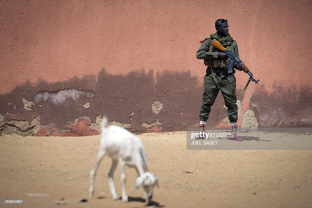 Malian army soldier Sekou Bolly, aged 30, holds an AK-47 assault rifle as he patrols on February 25, 2013 in Gao, some 1,200 kilometres (745 miles) north of Bamako. After recapturing the north's cities from the Al Qaeda groups that had controlled them since April 2012, the six-week-long French-led offensive took the fight to the retreating Islamist insurgents' toughest desert bastions.