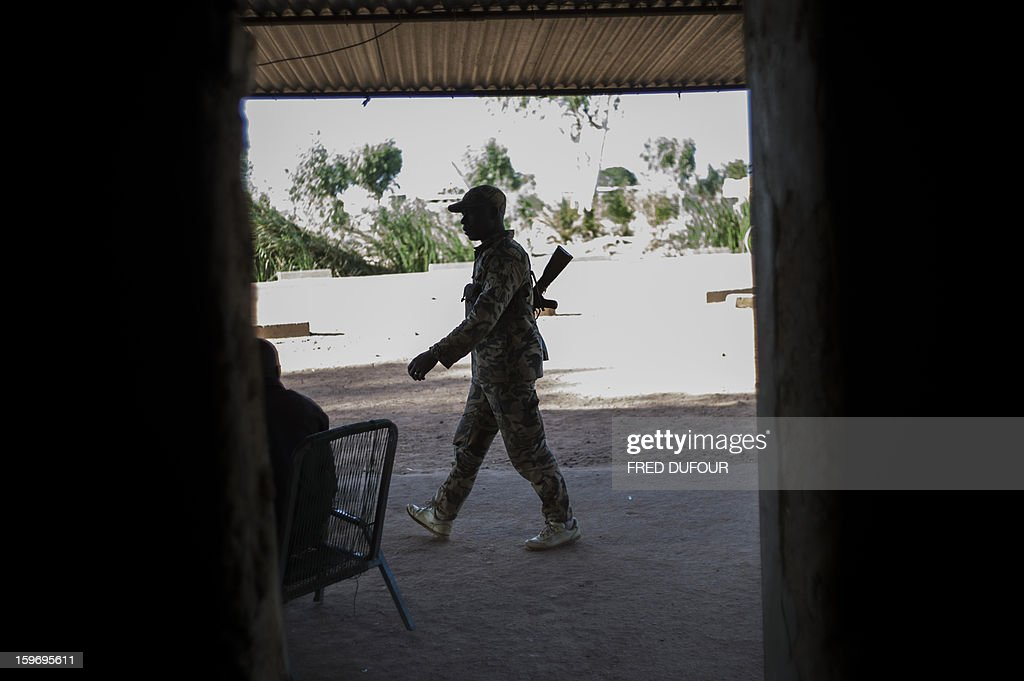 A Malian army soldier walks past an open doorway at a checkpoint in the city of Niono, on January 18, 2013. France now has 1,800 troops on the ground in Mali, inching closer to the goal of 2,500 it plans to deploy in its African former colony, Defence Minister Jean-Yves Le Drian said today. That was 400 more than a day earlier, said the minister as he met with French special forces in the western port of Lorient. The troops have been sent to help the Malian army regain control of the north from Islamist groups. AFP PHOTO / FRED DUFOUR