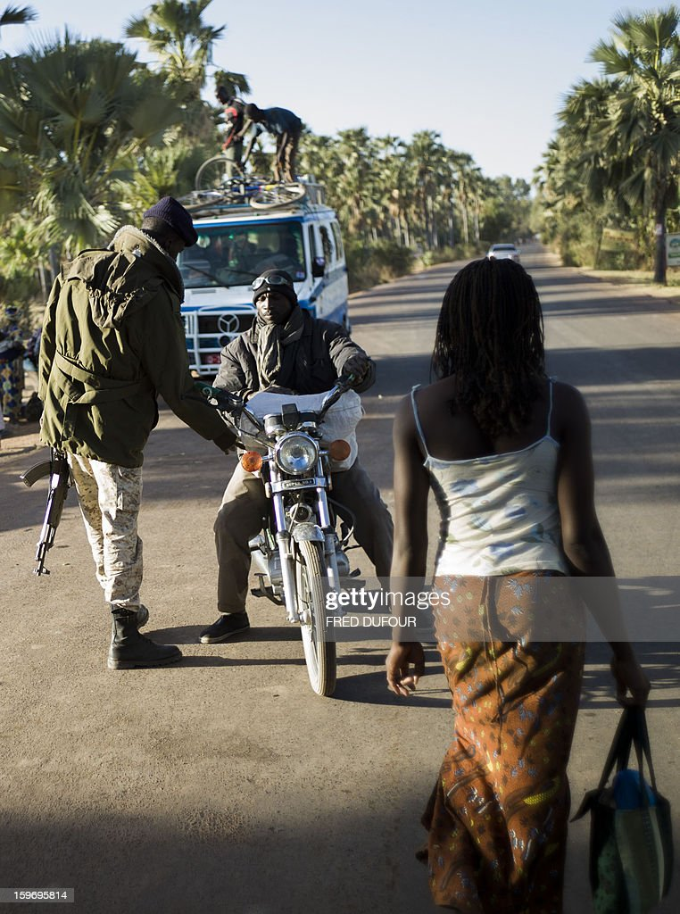 Malian army soldiers control a motorcycle driver at a checkpoint in Niono, on January 18, 2013. France now has 1,800 troops on the ground in Mali, inching closer to the goal of 2,500 it plans to deploy in its African former colony, Defence Minister Jean-Yves Le Drian said today. That was 400 more than a day earlier, said the minister as he met with French special forces in the western port of Lorient. The troops have been sent to help the Malian army regain control of the north from Islamist groups.
