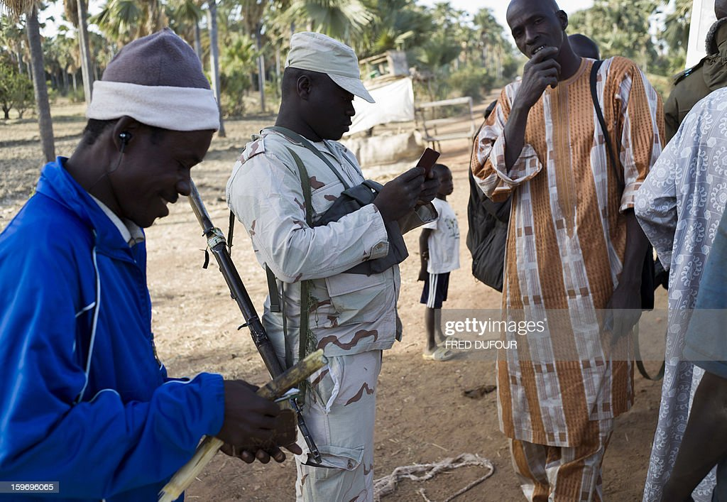 Malian army soldiers control people coming from the north at a checkpoint in Niono, 340kms north of Bamako, on January 18, 2013. France now has 1,800 troops on the ground in Mali, inching closer to the goal of 2,500 it plans to deploy in its African former colony, Defence Minister Jean-Yves Le Drian said today. That was 400 more than a day earlier, said the minister as he met with French special forces in the western port of Lorient. The troops have been sent to help the Malian army regain control of the north from Islamist groups. AFP PHOTO / FRED DUFOUR