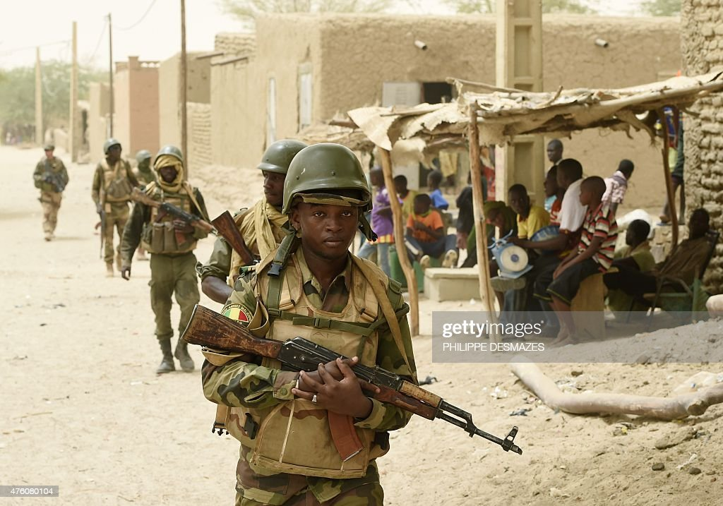 Malian army soldiers patrol after arresting two suspected looters in the village of Bintagoungou on June 4 near Goundam 80 km east of Timbuktu...