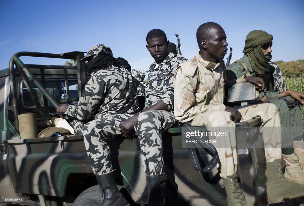 Malian army soldiers sit at the back of a pickup truck as they head towards Niono, 340kms north of Bamako, on January 18, 2013. France now has 1,800 troops on the ground in Mali, inching closer to the goal of 2,500 it plans to deploy in its African former colony, Defence Minister Jean-Yves Le Drian said today. That was 400 more than a day earlier, said the minister as he met with French special forces in the western port of Lorient. The troops have been sent to help the Malian army regain control of the north from Islamist groups.