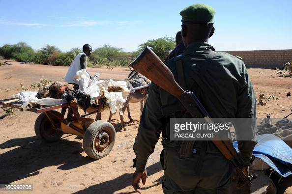 A Malian carries on a cart on February 8 2013 the corpse of a suicide bomber who blew himself up near a group of Malian soldiers in the northern city...