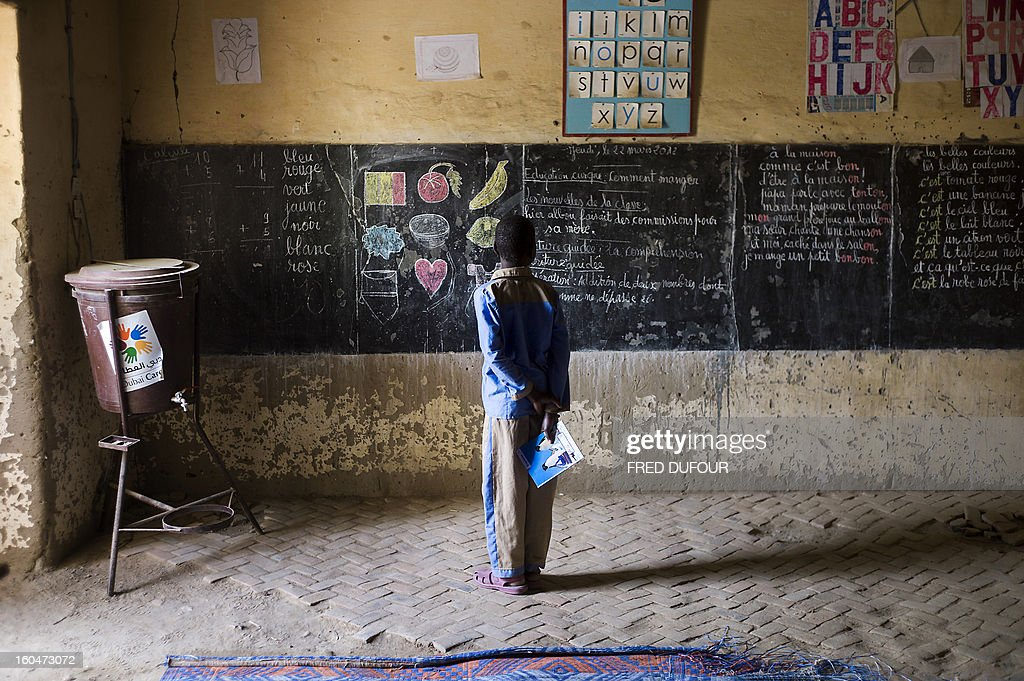 A Malian child stands in front of the black board of his school on February 1, 2013 in Timbuktu, indicating the last day of class on March 22, 2012, as the school re-open today after 10 months of islamists ruling in Northern Mali. French-led troops worked today to secure the last Islamist stronghold in the north after a lightning offensive against the extremists. AFP PHOTO / FRED DUFOUR