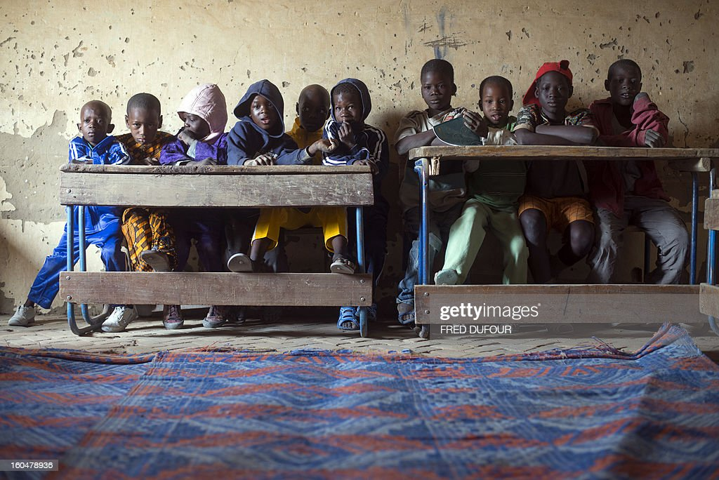 Malian children attend a class in a school of Timbuktu on February 1, 2013, which re-opens today after 10 months of islamists ruling in northern Mali. French-led troops worked today to secure the last Islamist stronghold in the north after a lightning offensive against the extremists. The fabled desert city of Timbuktu, an ancient centre of Islamic learning, has been recaptured on January 28 by French-led forces in their offensive against Islamist rebels who have been occupying Mali's north since last April.