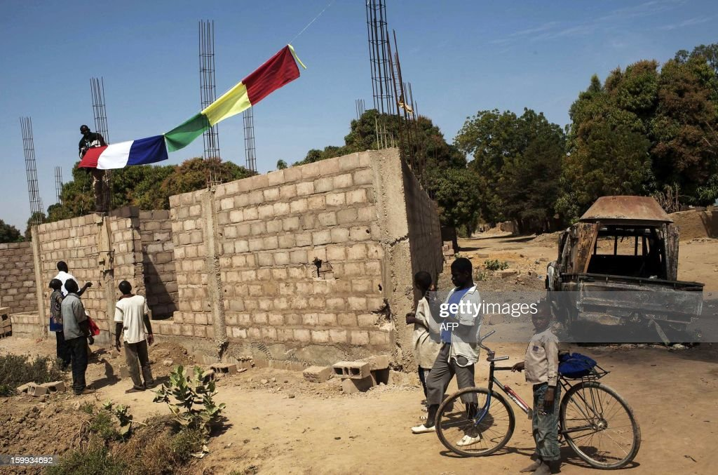 Malian citizens hang up French and Malian flags on January 23, 2013 along the road to Diabaly, which was seized last week by Islamists and then heavily bombed by French planes. The regional bloc, the Economic Community of West African States (ECOWAS), has pledged up to 4,000 troops to join a French-led intervention force to stop the advance of Islamist rebels based in northern Mali.