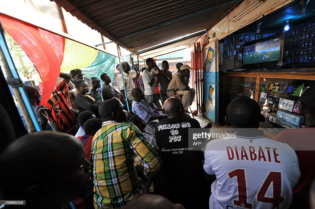 Malian citizens watch the 2013 Africa Cup of Nations football match between Mali and Ghana on a TV set on January 24, 2013 in the capital Bamako.