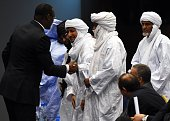 Malian Foreign Minister Abdoulaye Diop shakes hands with representatives of Malian armed rebel groups at the end of a peace agreement ceremony as...