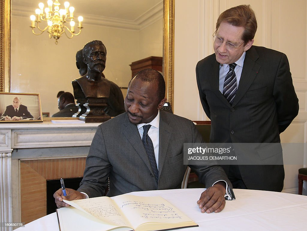 Malian Foreign Minister Tieman Coulibaly (L) looks on February 4, 2013 at the guest book with the interim administrator of Sciences Po university, Jean Gaeremynck, before giving a conference at the Paris School of International Affairs of the Paris school.