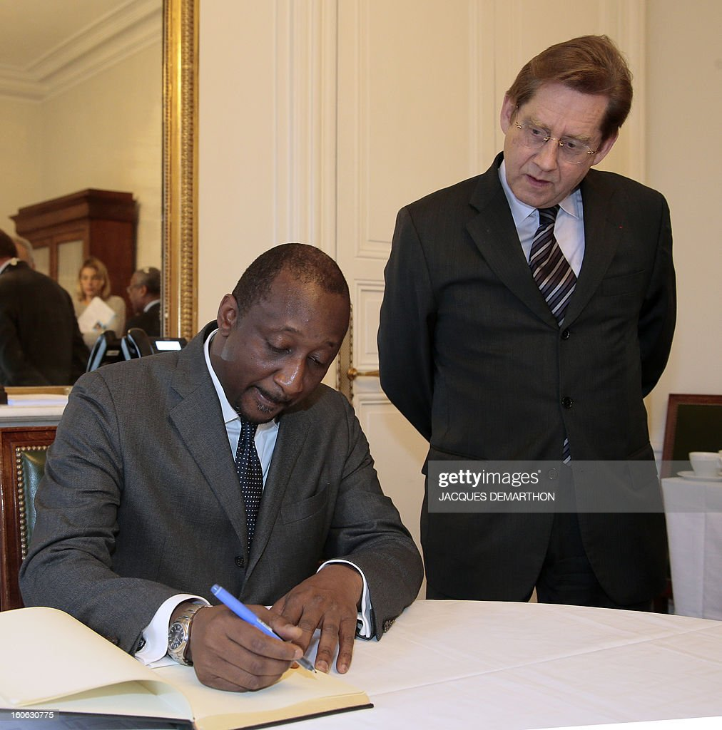 Malian Foreign Minister Tieman Coulibaly (L) signs on February 4, 2013 the guest book next to the interim administrator of Sciences Po university, Jean Gaeremynck, before giving a conference at the Paris School of International Affairs of the Paris school.