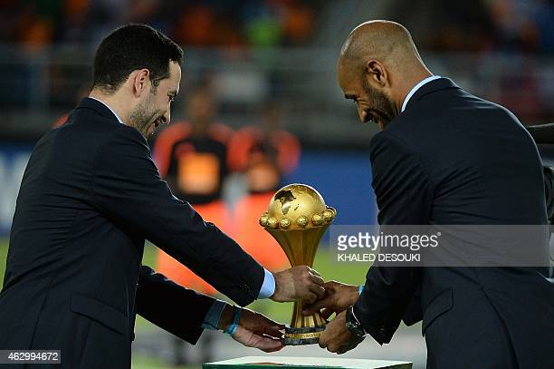 Malian forward Frederic Kanoute and Egyptian midfielder Mohamed Aboutrika deliver the 2015 African Cup of Nations trophy ahead of the final football...