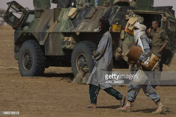 A Malian gendarme walks behind a prisoner on April 11 105 kms north of the northeastern Malian city of Gao in day four of Operation Gustav a hunt for...
