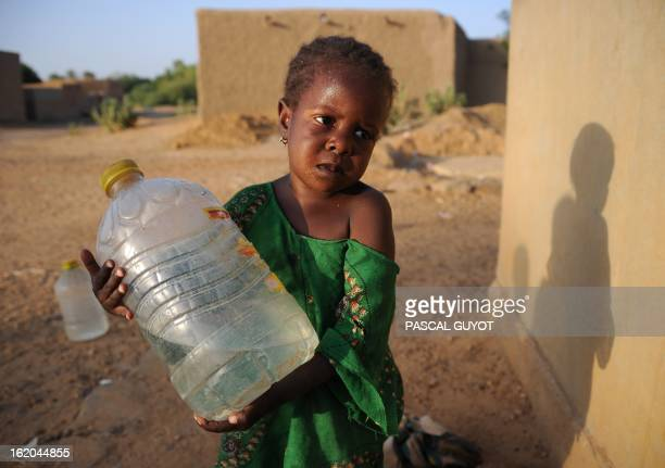 A Malian girl carries a water can she just partially filled at a water pump on February 18 2013 in northern Mali's city of Gao as European Union...