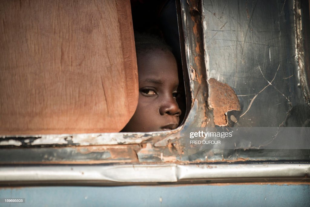 A Malian girl looks out from a bus as Malian army soldiers prepare to check the vehicule and passengers at a checkpoint in the city of Niono, on January 18, 2013. France now has 1,800 troops on the ground in Mali, inching closer to the goal of 2,500 it plans to deploy in its African former colony, Defence Minister Jean-Yves Le Drian said today. That was 400 more than a day earlier, said the minister as he met with French special forces in the western port of Lorient. The troops have been sent to help the Malian army regain control of the north from Islamist groups. AFP PHOTO / FRED DUFOUR