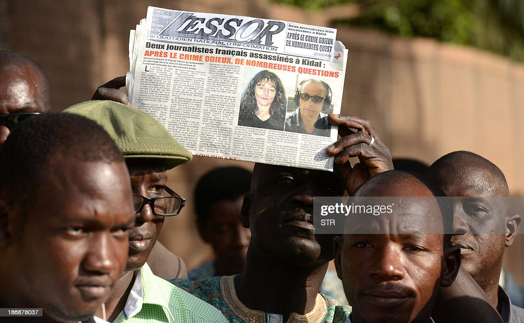 A Malian journalist holds a local newspaper showing on frontpage the portraits of Radio France Internationale (RFI) journalist Ghislaine Dupont and sound technician Claude Verlon killed in the town of Kidal, as he takes part with other Malian journalists in a white march in their memory on November 4, 2013 in Bamako. French troops were working today with Malian security forces to hunt the killers of the two French journalists shot dead in the west African nation's rebel-infested northern desert. Ghislaine Dupont, 57, and Claude Verlon, 55, were kidnapped and killed by what French Foreign Minister Laurent Fabius said were 'terrorist groups' in the flashpoint northeastern town of Kidal on November 2, 2013.