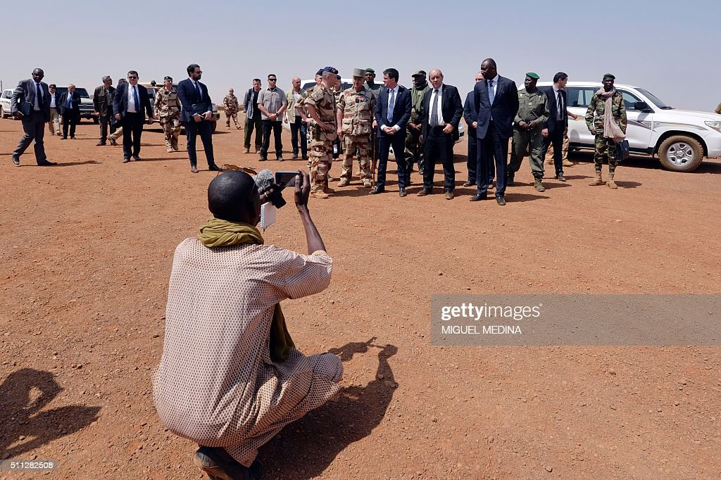 A Malian journalist takes a picture of French Prime Minister Manuel Valls France Defense Minister JeanYves Le Drian and Mali Defense Minister Tieman...