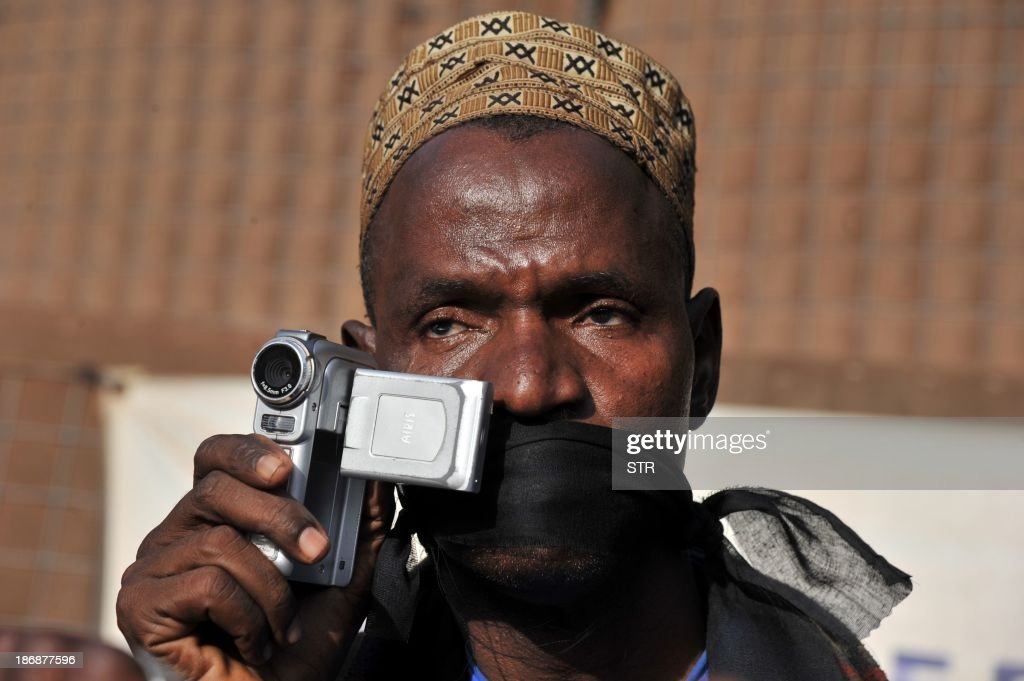 A Malian journalist with a black gag on his mouth holds a video camera as he takes part in a white march with other Malian journalists on November 4, 2013 in Bamako, in memory of Radio France Internationale (RFI) journalist Ghislaine Dupont and sound technician Claude Verlon killed in the town of Kidal. French troops were working today with Malian security forces to hunt the killers of the two French journalists shot dead in the west African nation's rebel-infested northern desert. Ghislaine Dupont, 57, and Claude Verlon, 55, were kidnapped and killed by what French Foreign Minister Laurent Fabius said were 'terrorist groups' in the flashpoint northeastern town of Kidal on November 2, 2013.