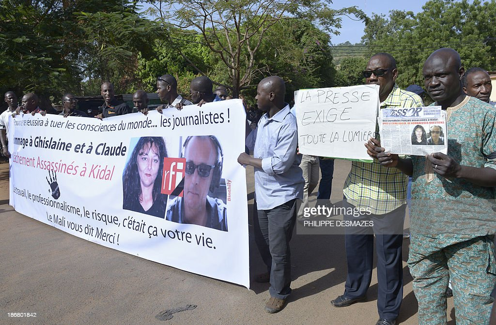 Malian journalists hold a banner and placards during a white march on November 4, 2013 in Bamako, in memory of Radio France Internationale (RFI) journalist Ghislaine Dupont (L) and sound technician Claude Verlon (R) killed in the town of Kidal. French troops were working today with Malian security forces to hunt the killers of the two French journalists shot dead in the west African nation's rebel-infested northern desert. Ghislaine Dupont, 57, and Claude Verlon, 55, were kidnapped and killed by what French Foreign Minister Laurent Fabius said were 'terrorist groups' in the flashpoint northeastern town of Kidal on November 2, 2013.